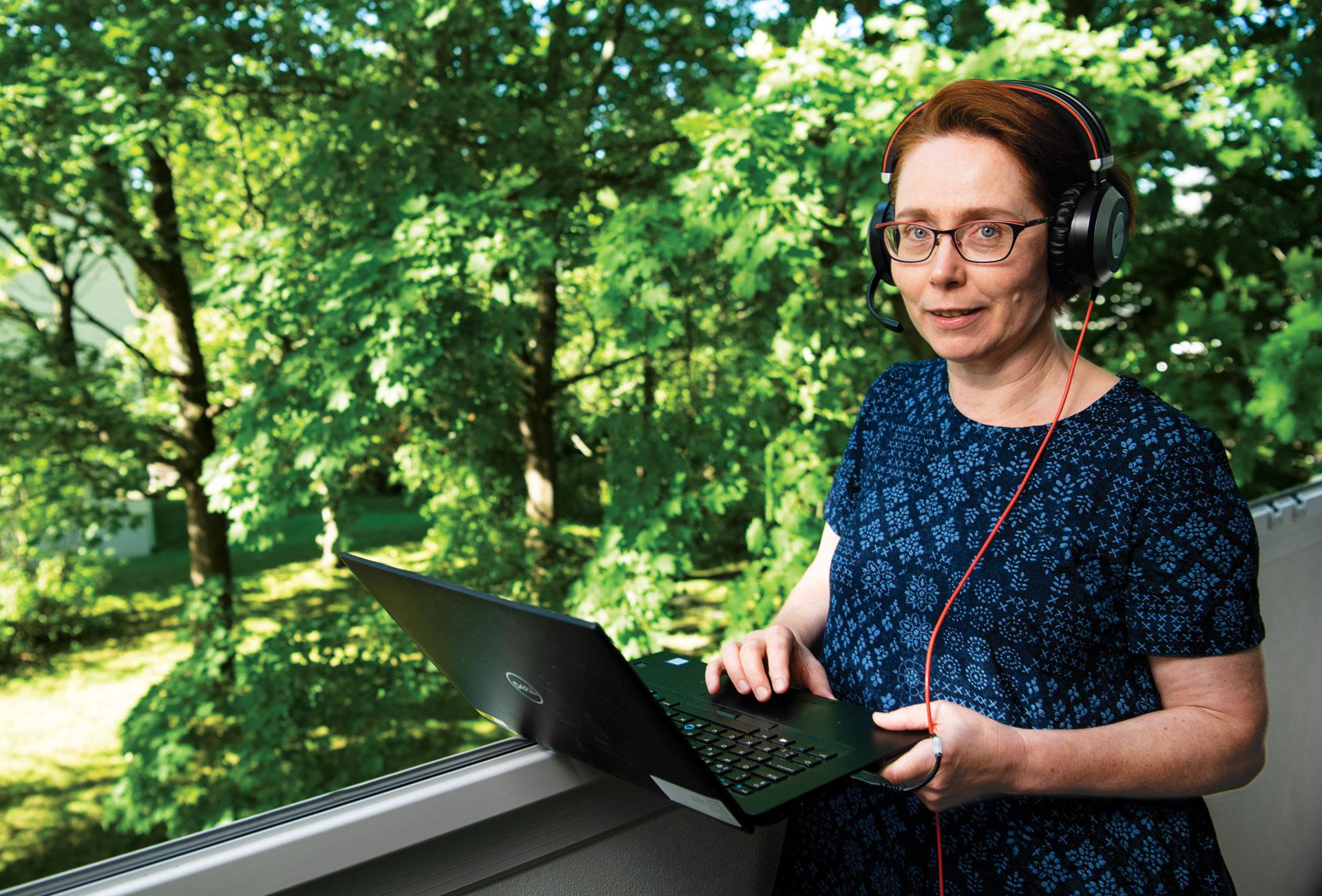 Kirsi Valanne parvekkeella kannettavan tietokoneen kanssa