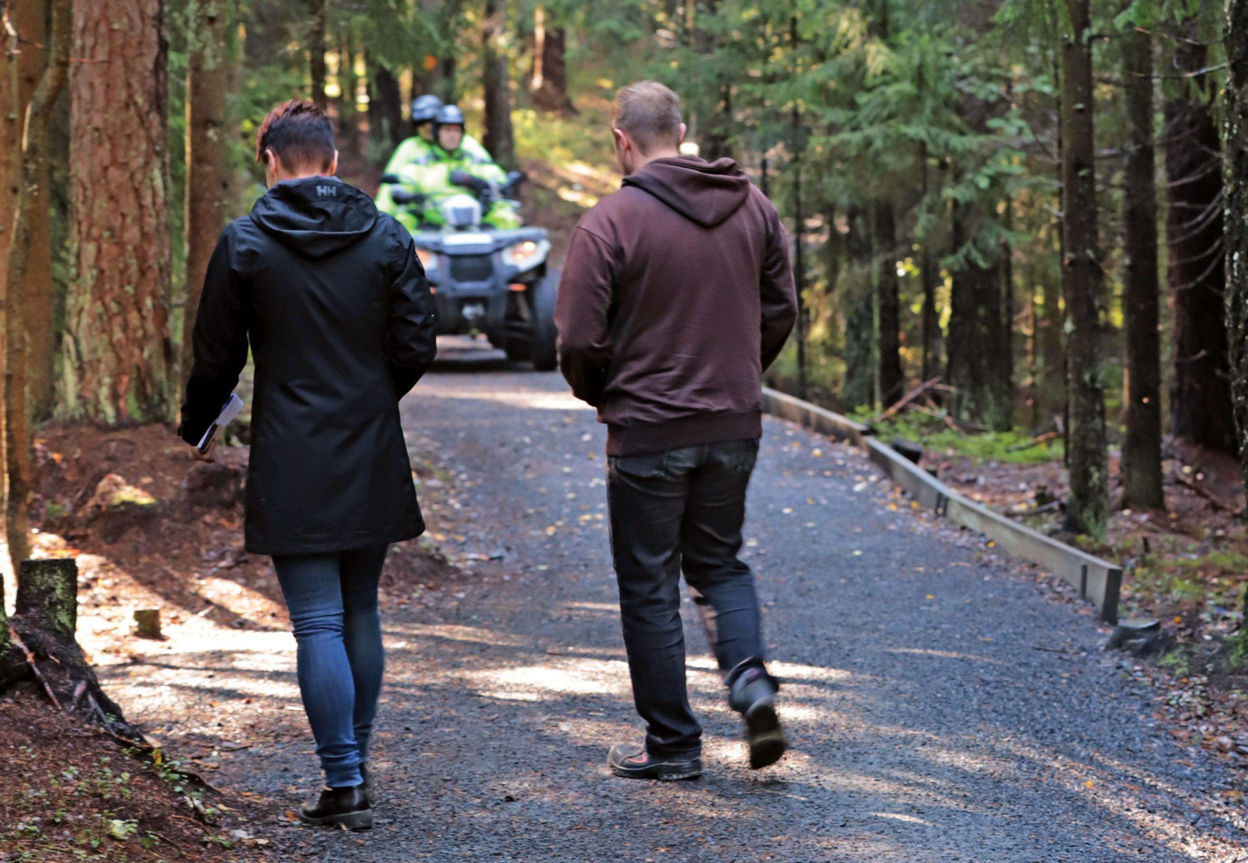 Kävelijöitä metsäpolulla, taustalla mönkijä
